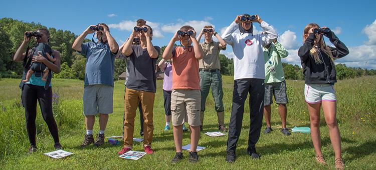 People using binoculars at a Minnesota state park naturalist program.