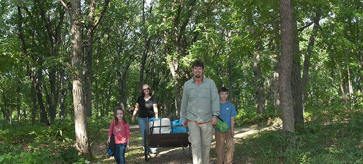 Family hiking to a cart-in campsite
