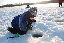 Child peering into ice fishing hole.