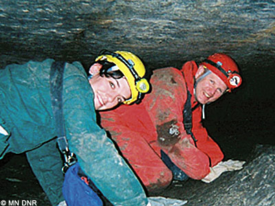 Cavers crawling through a tight passage.