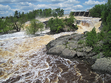 Coffee colored water cascading down rock formations in Jay Cooke State Park.