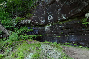 Photo of sandstone outcrops along a challenging trail with narrow passages and steep drops.