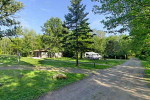 Photo of a wooded campground that offers campsites (some electric) and a restroom/shower facility.