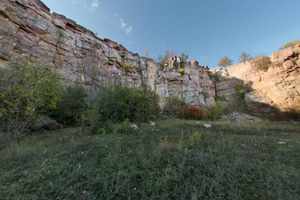 View of tall rocky quarry walls from the bottom of the quarry.