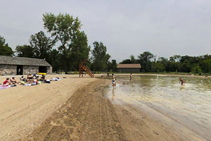 Photo of the swimming beach along the man-made pond, lined with soft sand and clean, filtered river water.