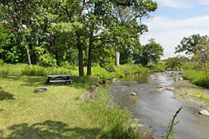 Photo of a riverside campsite along the along the water.