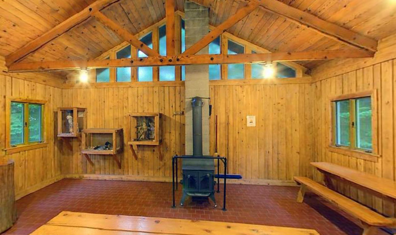 Photo of the wood-paneled trail center, which features picnic tables and a woodstove.