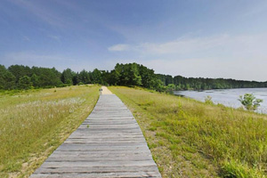 Photo of a sunny boardwalk along the Crow Wing River.