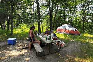 Photo of campers clustered around the picnic table located near the river.
