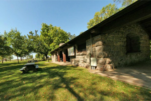 Photo of the stone picnic shelter and picnic area.