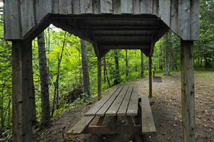 Photo of an Adirondack-style picnic table shelter located at a rustic campsite.