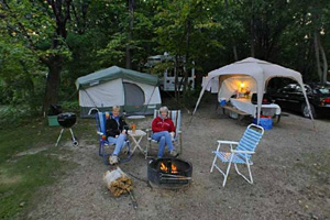 Photo of visitors enjoying an evening by the campfire shady at one of the park's electric campsites.