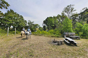 Photo of horseback riders visiting the Baby Lake hike-in site, which features a single tie post, picnic table, fire ring.