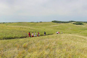 Photo of a group of visitors hiking along a trail in the prairie landscape and rolling hills.