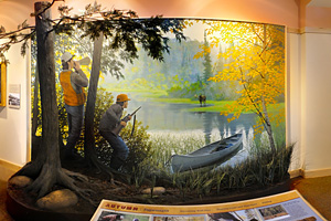 Photo of a mural which depicts Ojibwe men on a present day moose hunt.