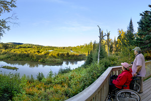 Photo of a wooden deck with a view across the Pigeon River into Ontario, Canada.