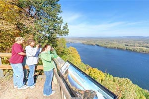 Photo of three people enjoying the scenery from Great River Bluff State Park's East Overlook.