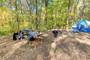 Photo of Group Campsite #1 at Great River Bluffs State Park, with a family in the background setting up their tent and other gear.