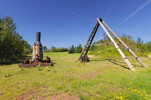 Photo of a team drill and large, wooden tripod that were used for exploratory drilling.