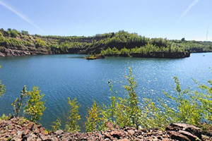 Photo of an old mine pit where hidden beneath the water's surface, is an old loading facility.
