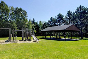 Photo of nearby city park offering a small playground and picnic tables to visitors.