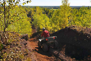 Photo of an all-terrain vehicle driver entering the recreation area's Red Valley by trail.