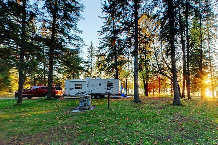 Photo of a truck and camper set up at the Itasca State Park RV campground.
