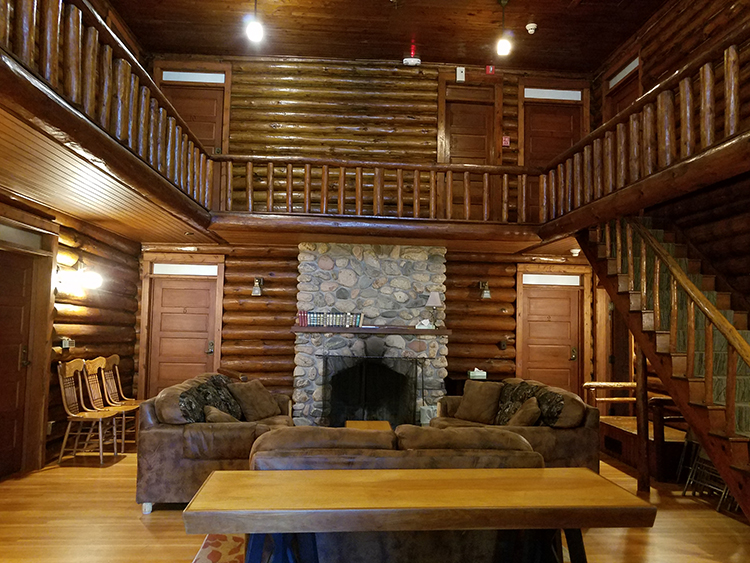 Photo of the Clubhouse interior, featuring a log staircase and stone fireplace.