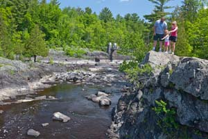 Photo of a family exploring the rocks at the side of the river.