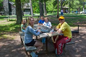 Photo of a family seated at a picnic table.