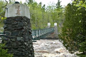 Photo of the swinging bridge over choppy water.