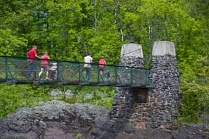 Photo of people crossing the swinging bridge on foot.
