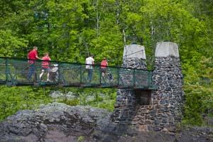 Photo of people crossing the swinging bridge on foot.