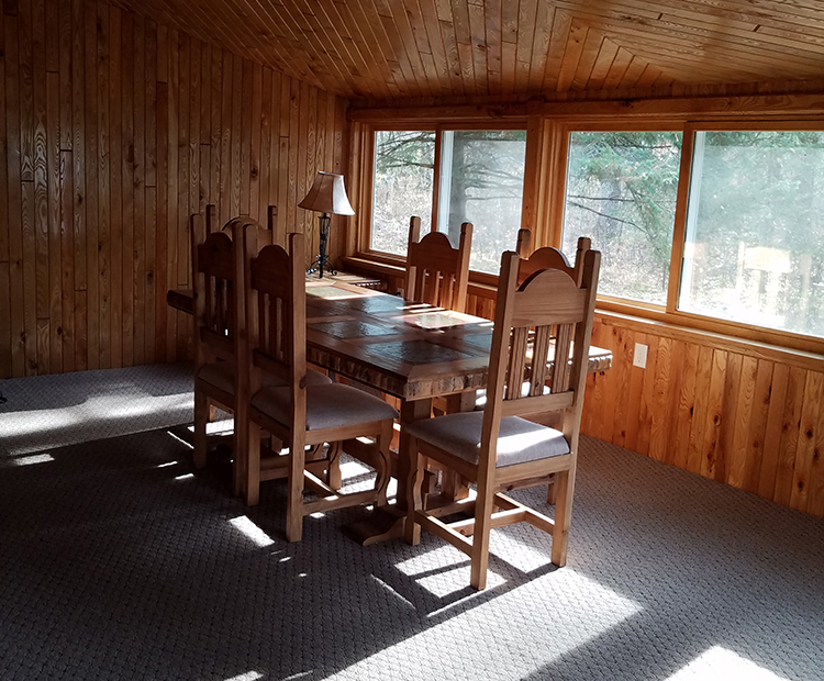 Photo of the spacious sun room and deck inside the Black Bear Cabin.