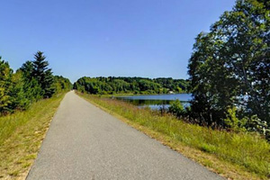 Photo of the paved trail segment above Big Bass Lake created from an old railroad grade.