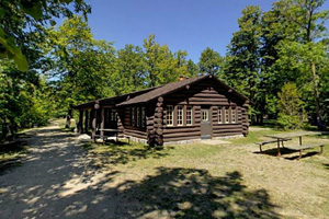 Photo of a historic, rustic picnic shelter located just a few steps from the water's edge.