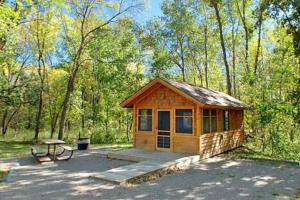 Photo of a camper cabin nestled in the woods.