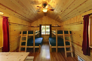 Photo of the interior of one of the cozy cabins with wood interiors, bunk beds and numerous windows.