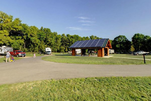 Photo of a picnic shelter, outfitted with a solar panel on the roof located in the Sunrise Campground.