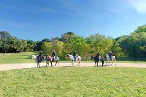 Photo of a row of equestrians heading out for a ride at Maplewood State Park.