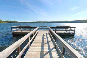 Photo of the long wooden fishing pier on Beers Lake, in Maplewood State Park.