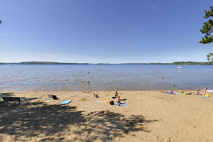 Photo of the sugar sand beach and long expanse of shallow water where park visitors relax along the lakeshore.