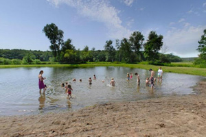 Photo of the park's swimming area, showing visitors enjoying the beach.