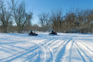 Photo of snowmobilers traveling along the frozen river near Thompson Ferry.