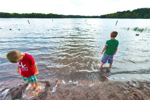 Photo of two young boys wading at the Moose Lake swimming beach.