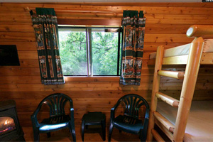 Photo of the interior inside a camper cabin with chairs, stove and bunks.
