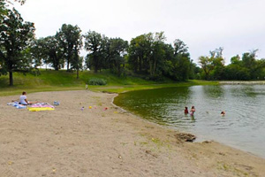 Photo of visitors using the park's swimming beach, created from fresh well water.