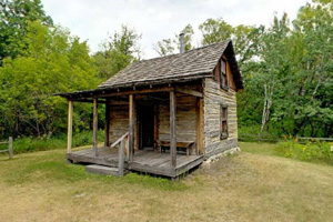Photo of a historic settler's cabin containing items illustrating pioneer family life.