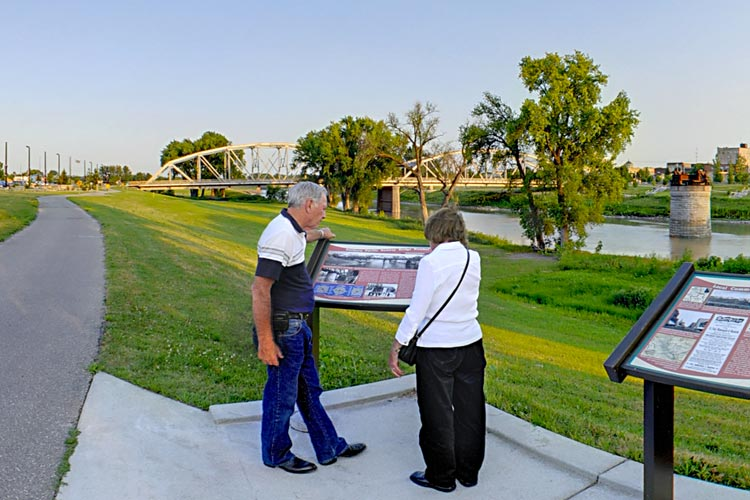 Photo of visitors viewing an interpretive plaque along the Greenway Trail.