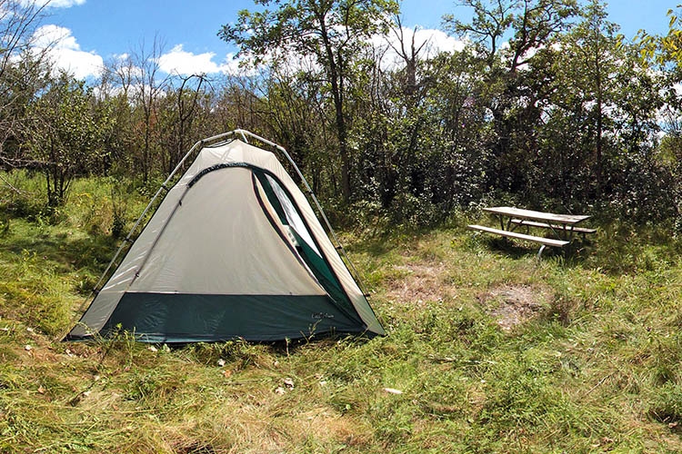 Photo of a tent camper using one of the primitive campsite locations.